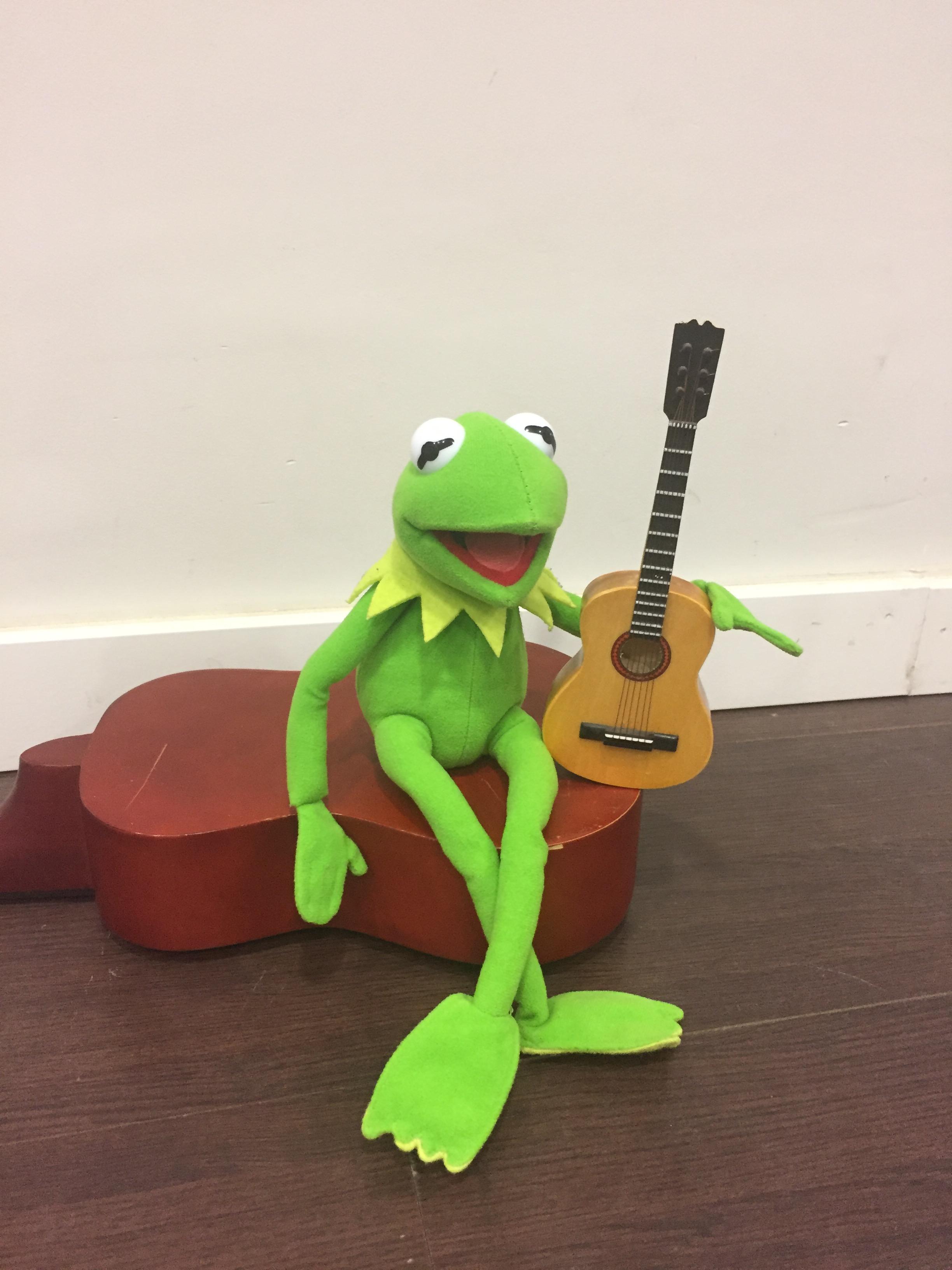 Un peluche de la rana Gustavo con una guitarra.
